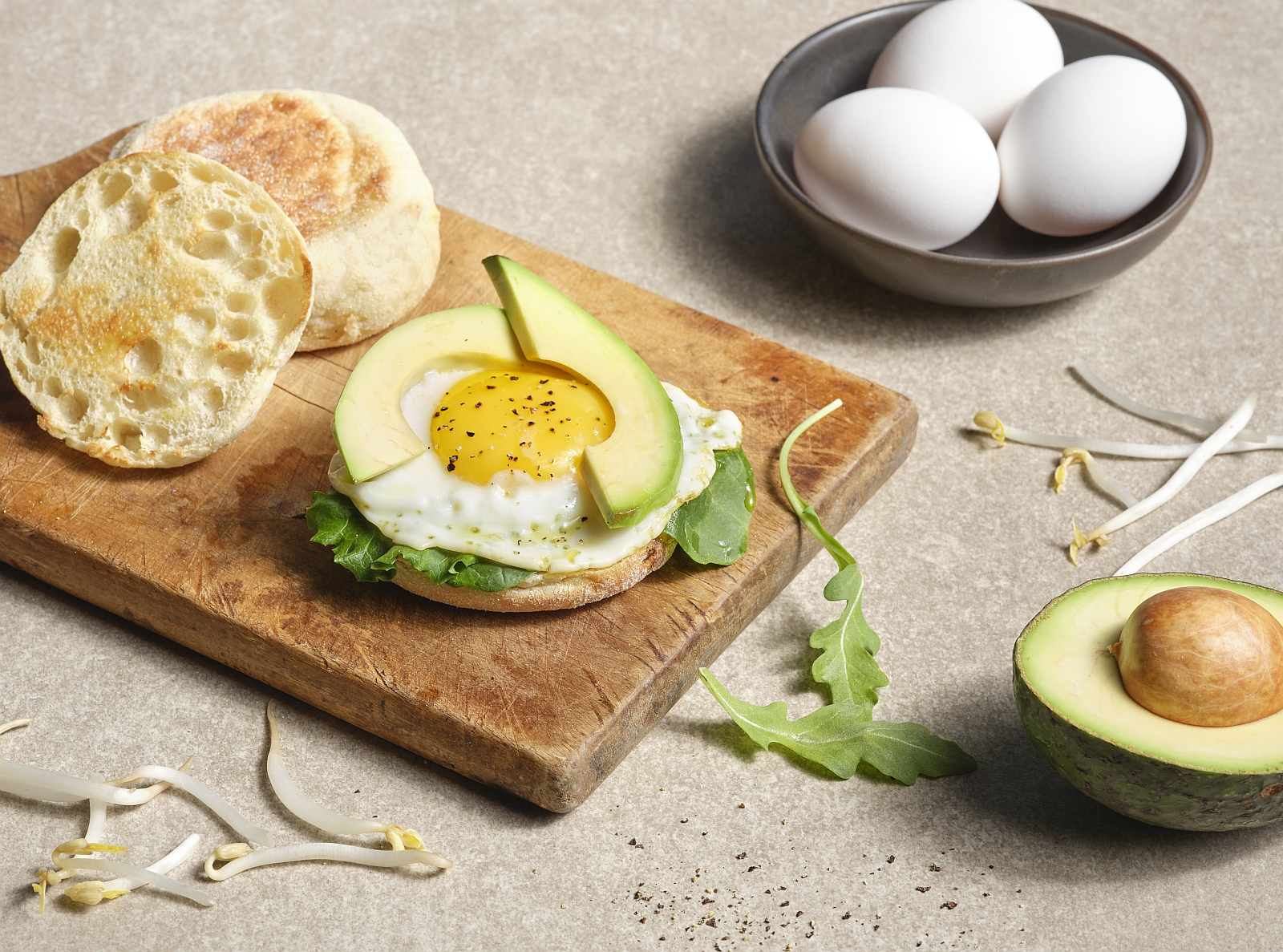 egg with avocado slices and english muffin