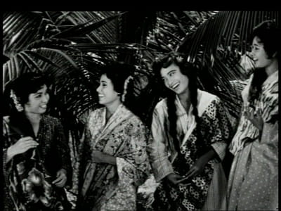 A black and white film still from the movie, 'Tun Fatimah'. Four women are smiling at each other.