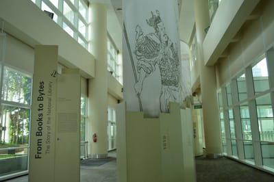 Photo of the front entrance of the From Books to Bytes gallery. A tall cloth banner hangs over the exhibition, with random book illustrations printed on it.