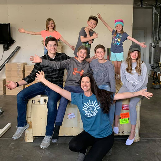 family of eight, with big smiles and extended arms, posing around a giant crate containing an Aeon CO2 laser inside.