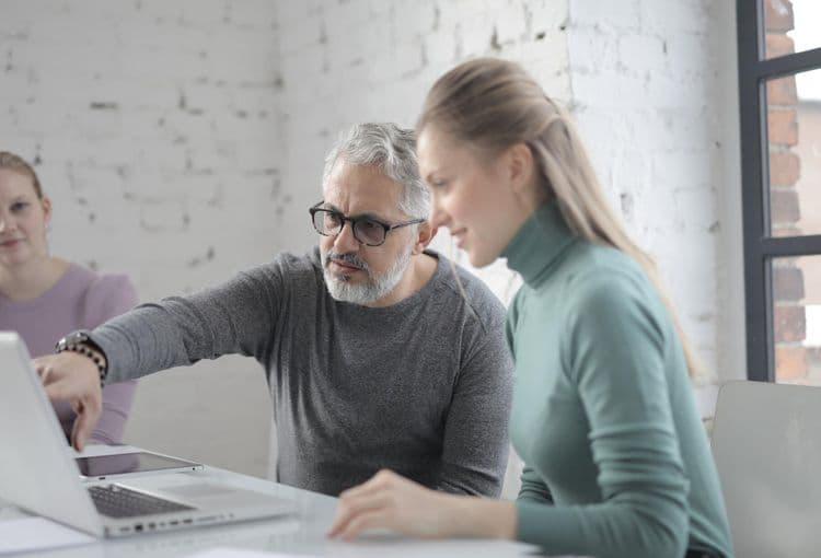 Trainer erklärt Inhalte auf einem Laptop