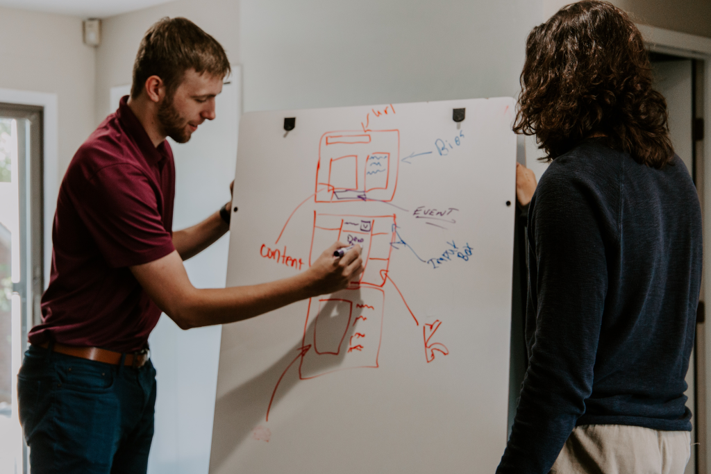 Two people reviewing diagrms written on a white board