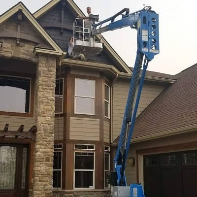 man on crane lift painting a two story home