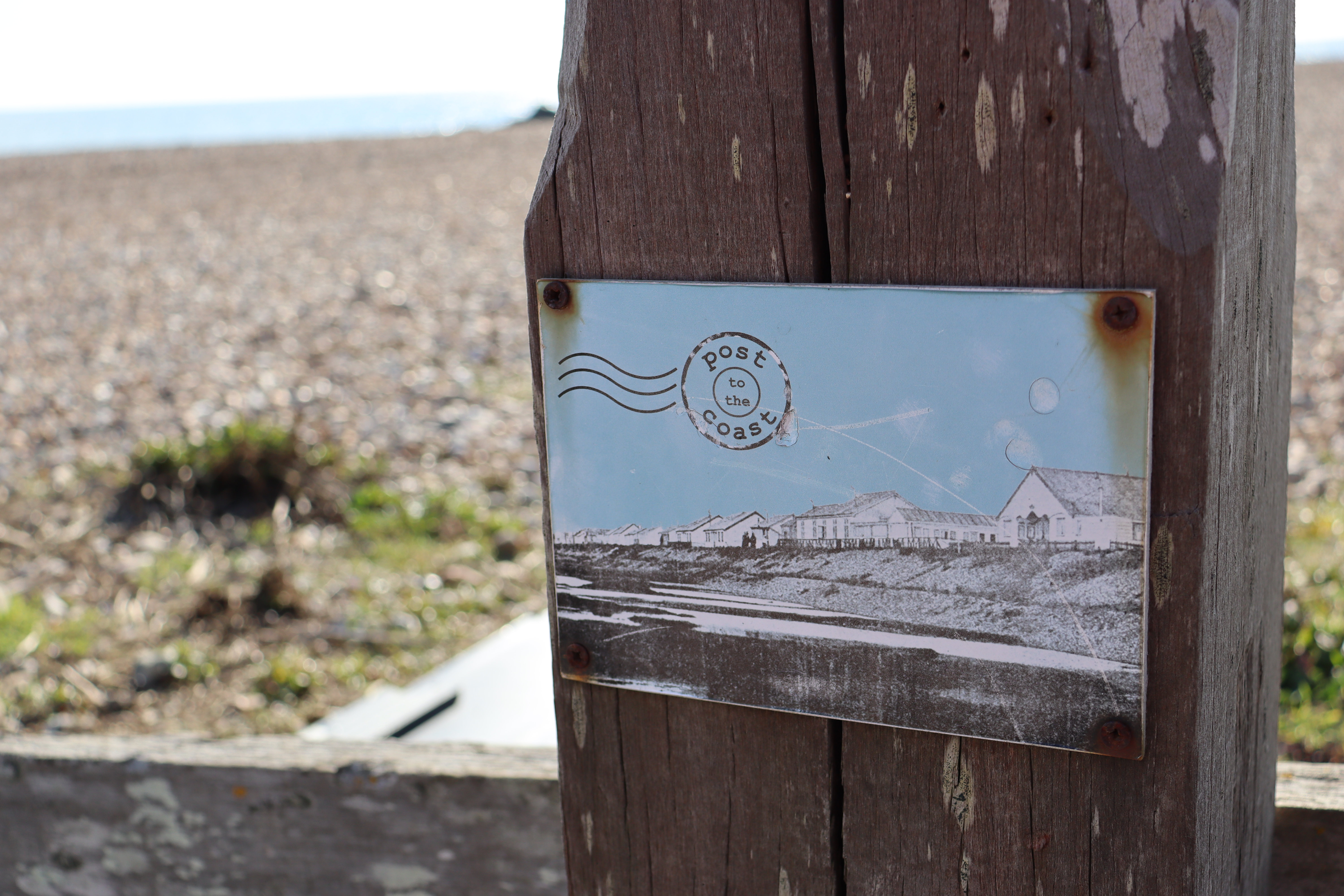 A black and white ceramic postcard attached to a wooden post with rusted screws.