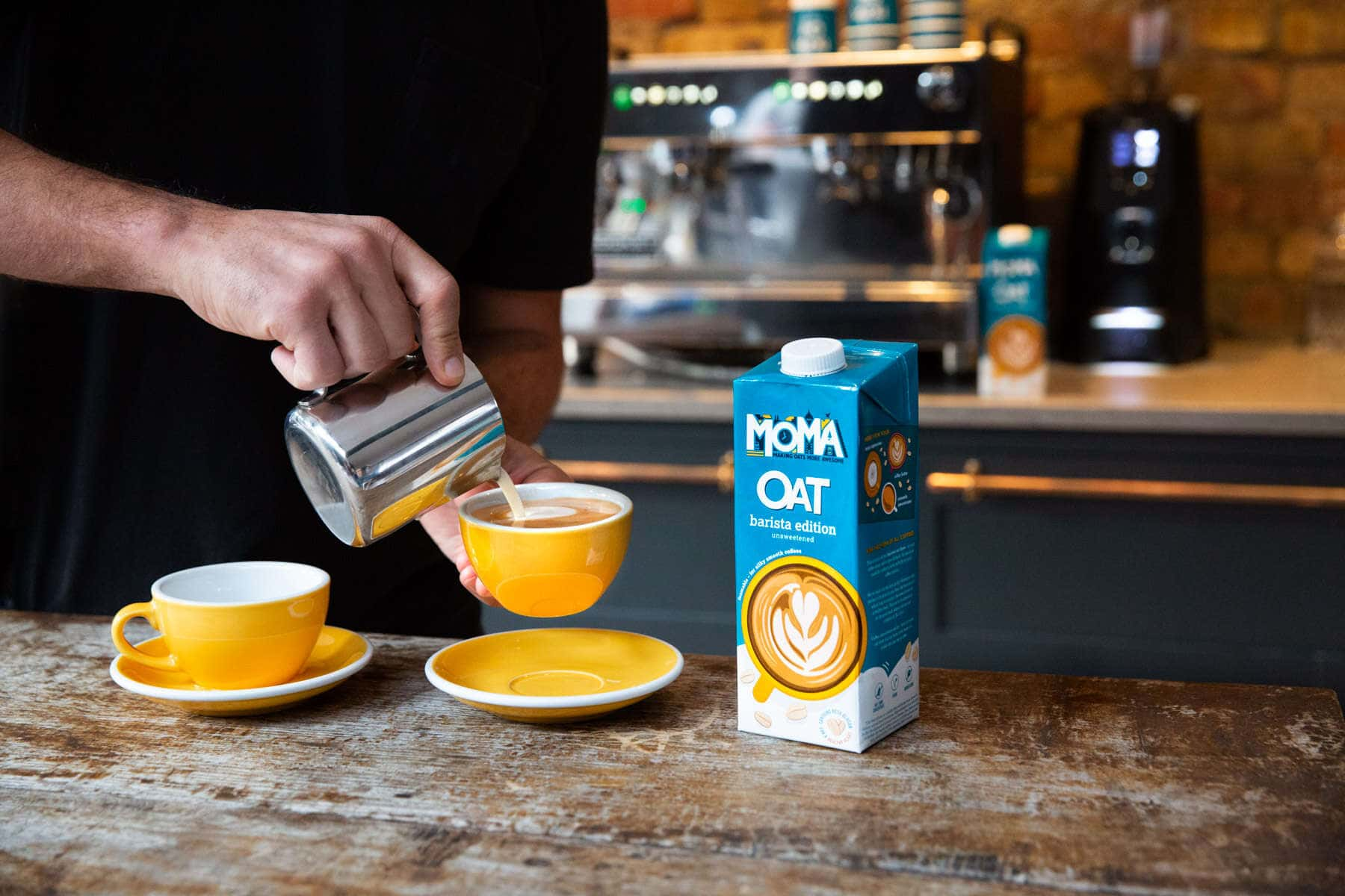Moma barista oat milk being poured in front of a coffee machine in a cafe