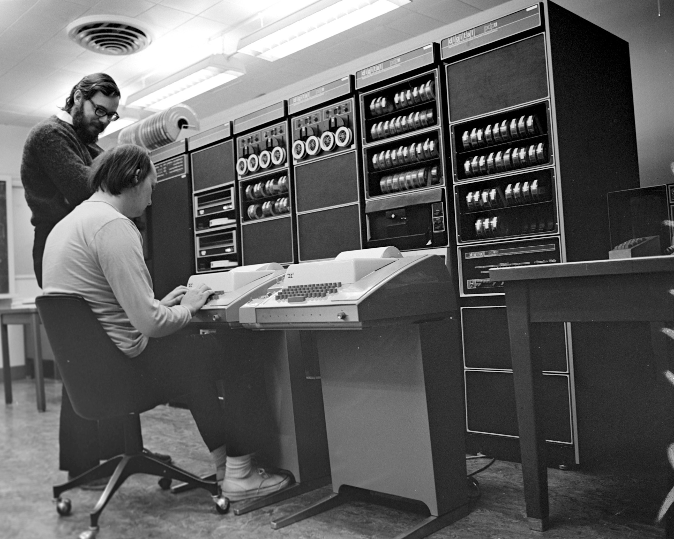Ken Thompson and Dennis Ritchie sitting at a teletype in front of a PDP-11