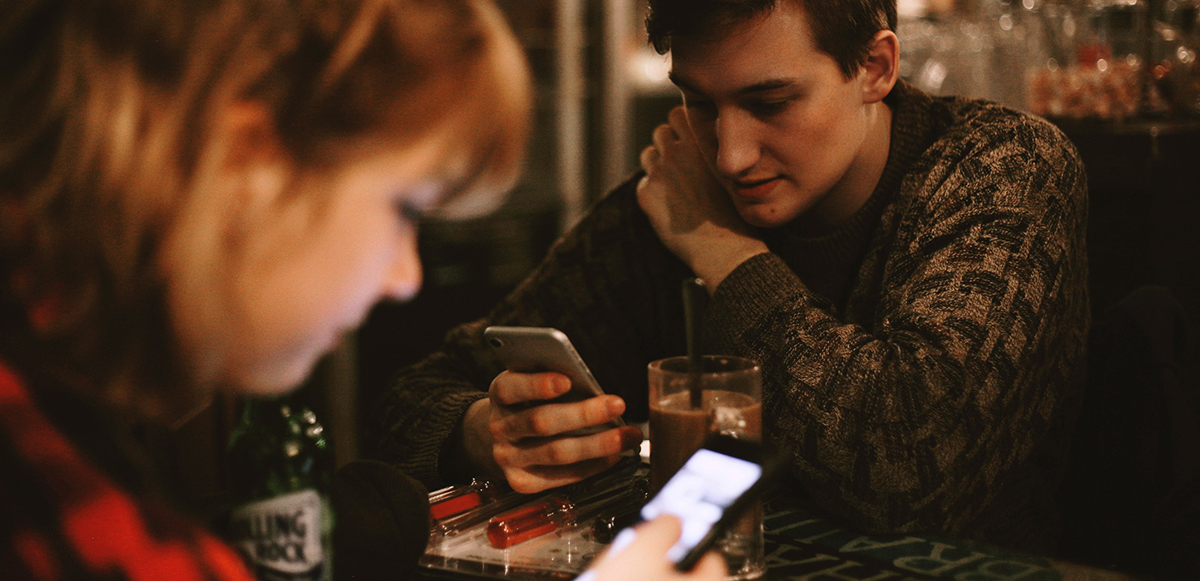 Man and women sitting on a bar table and looking at their cell phones