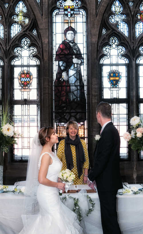 A couple getting married by a stain glass window