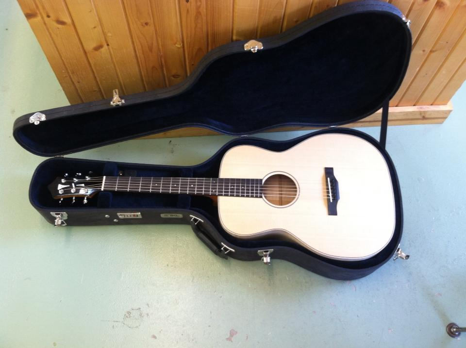 Image of an acoustic guitar in a case on the floor
