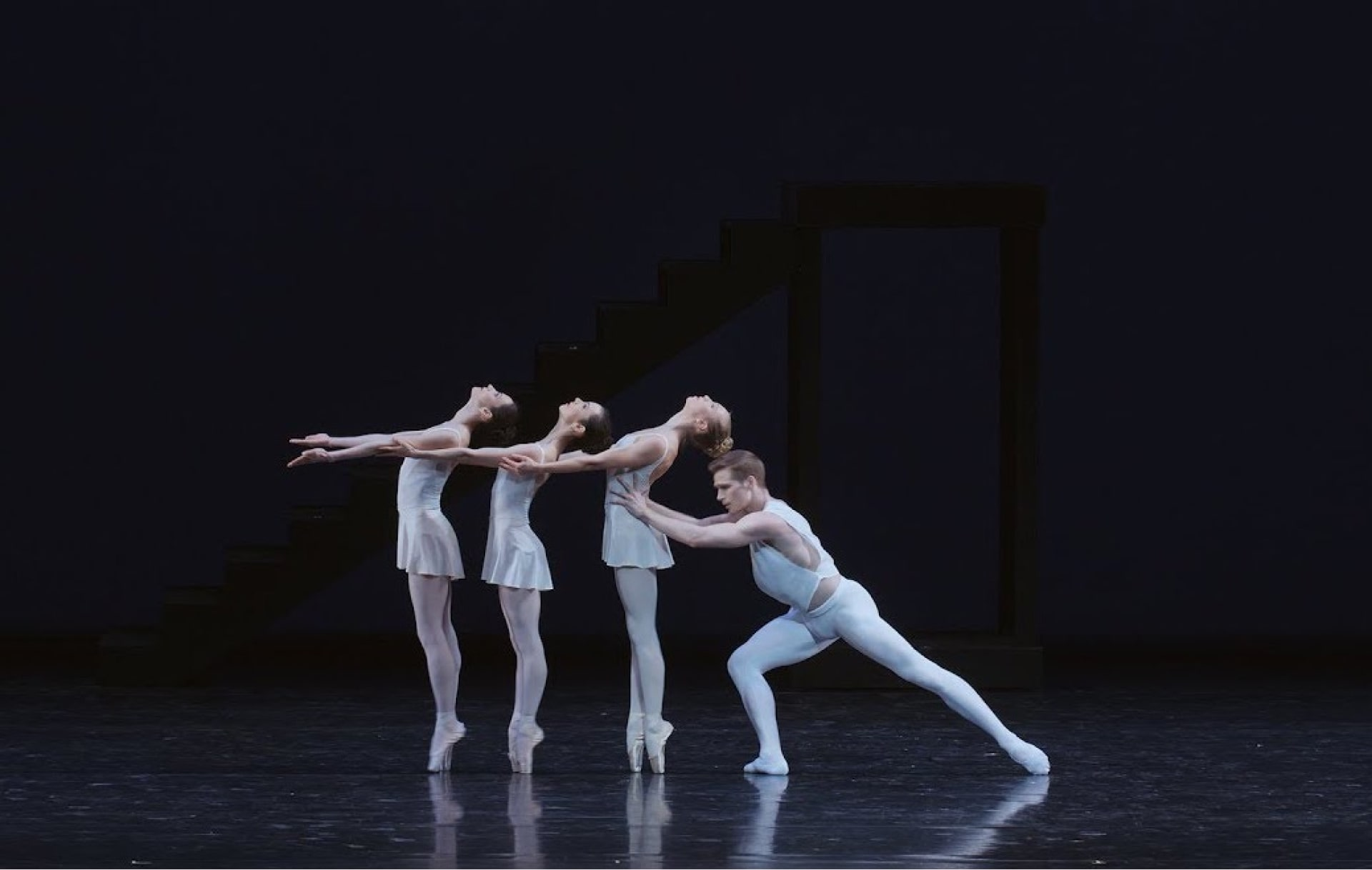 Bare-armed dancer in white tights steadies three ballerinas on point with outstretched arms.