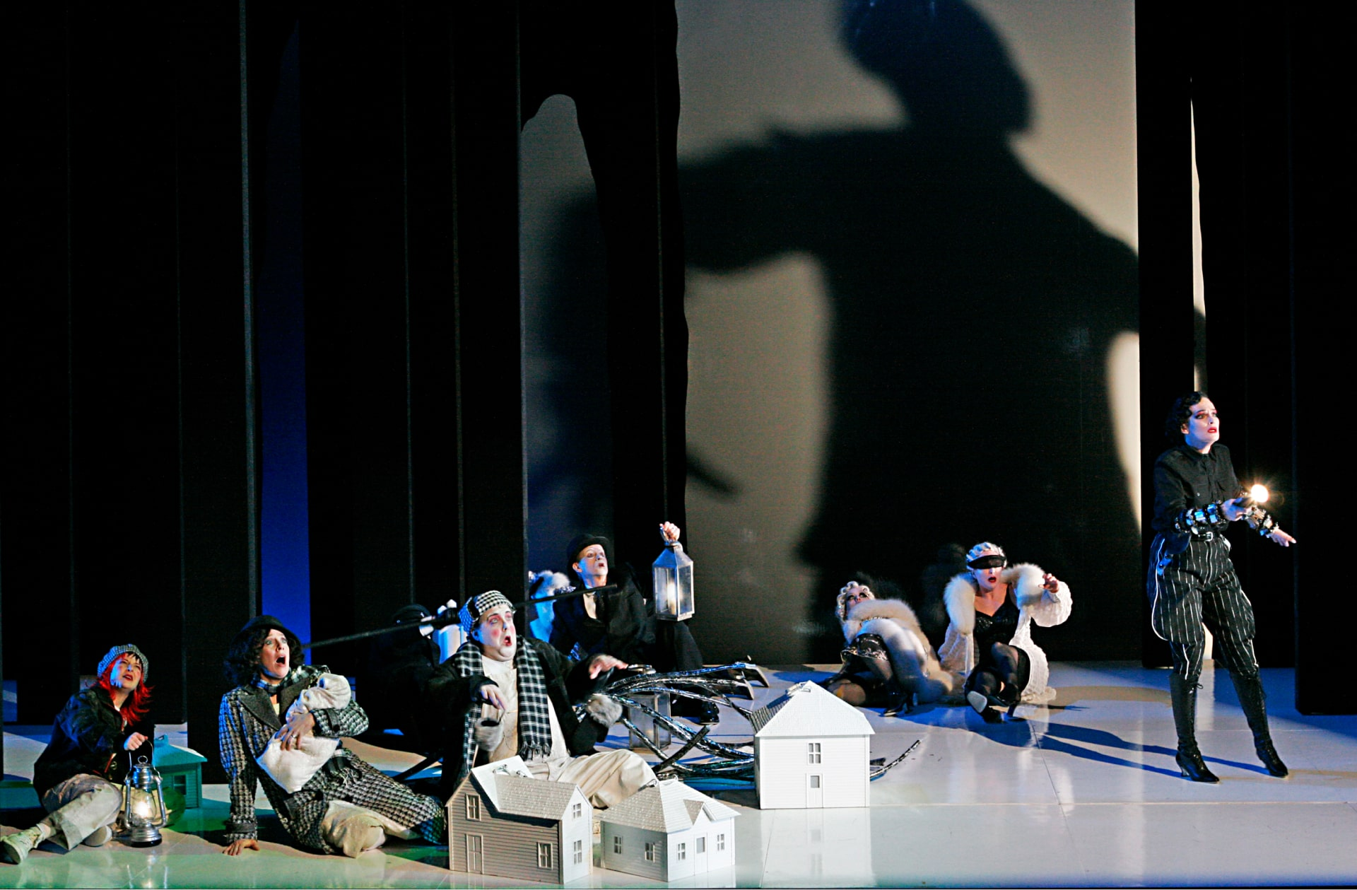 Various fable characters recoil on floor amongst model houses in front of giant shadow of human form.