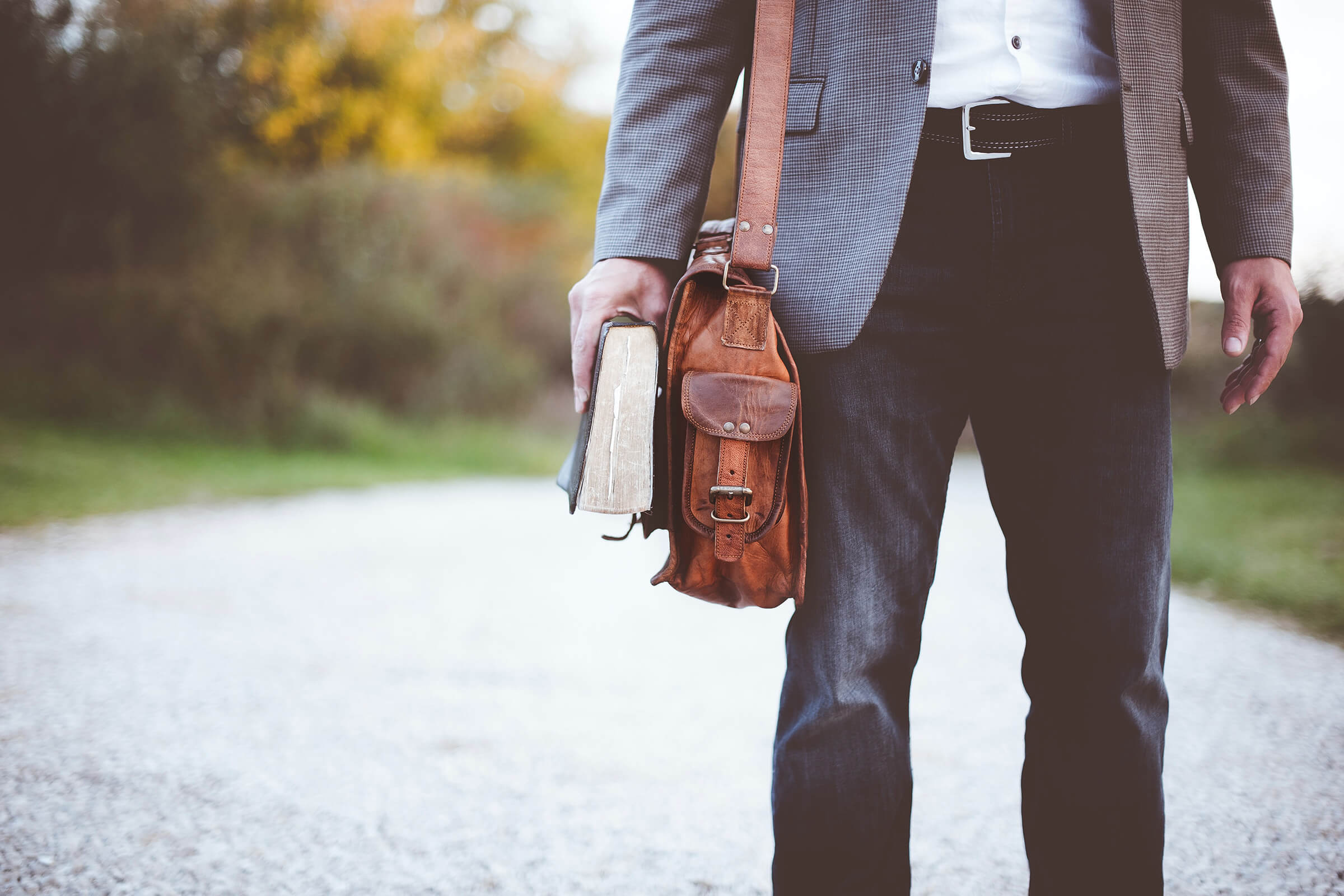 Stock photo of a man in jeans with a book and messenger bag