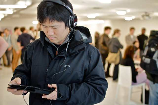 A man wears headphones and hold an iPad, listening to the aural game.