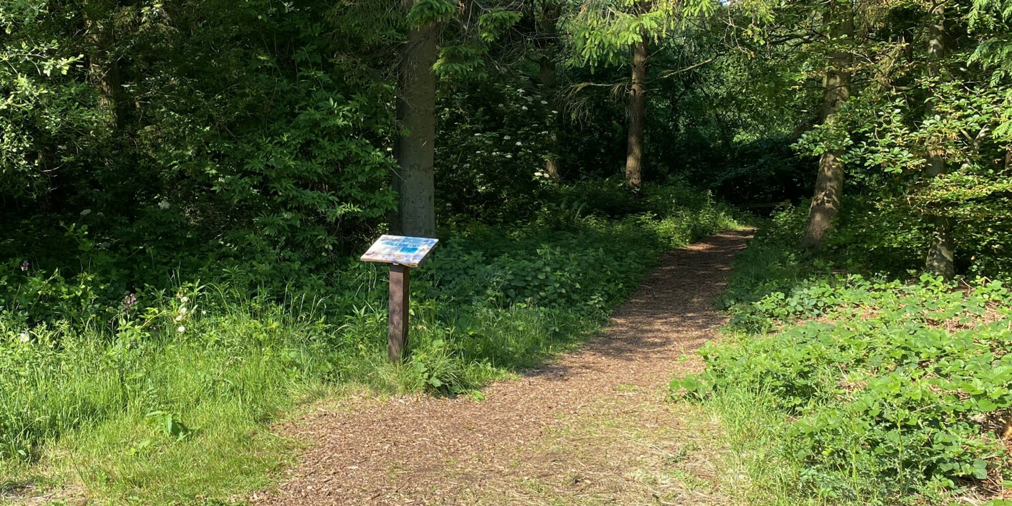 A sign by a path at Golden Acre Park