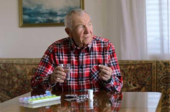 A man preparing to take a pill
