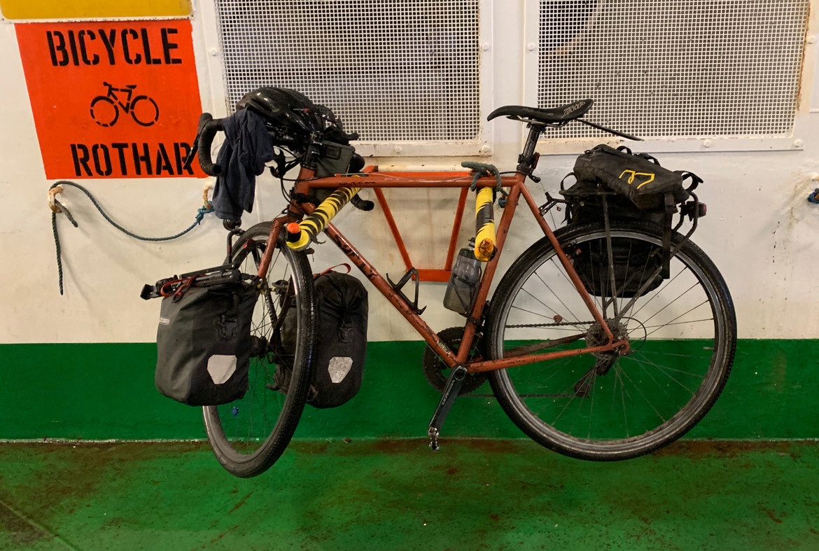 Touring bike on a nice two-pronged rack supporting the top bar and with an easy knot on one end