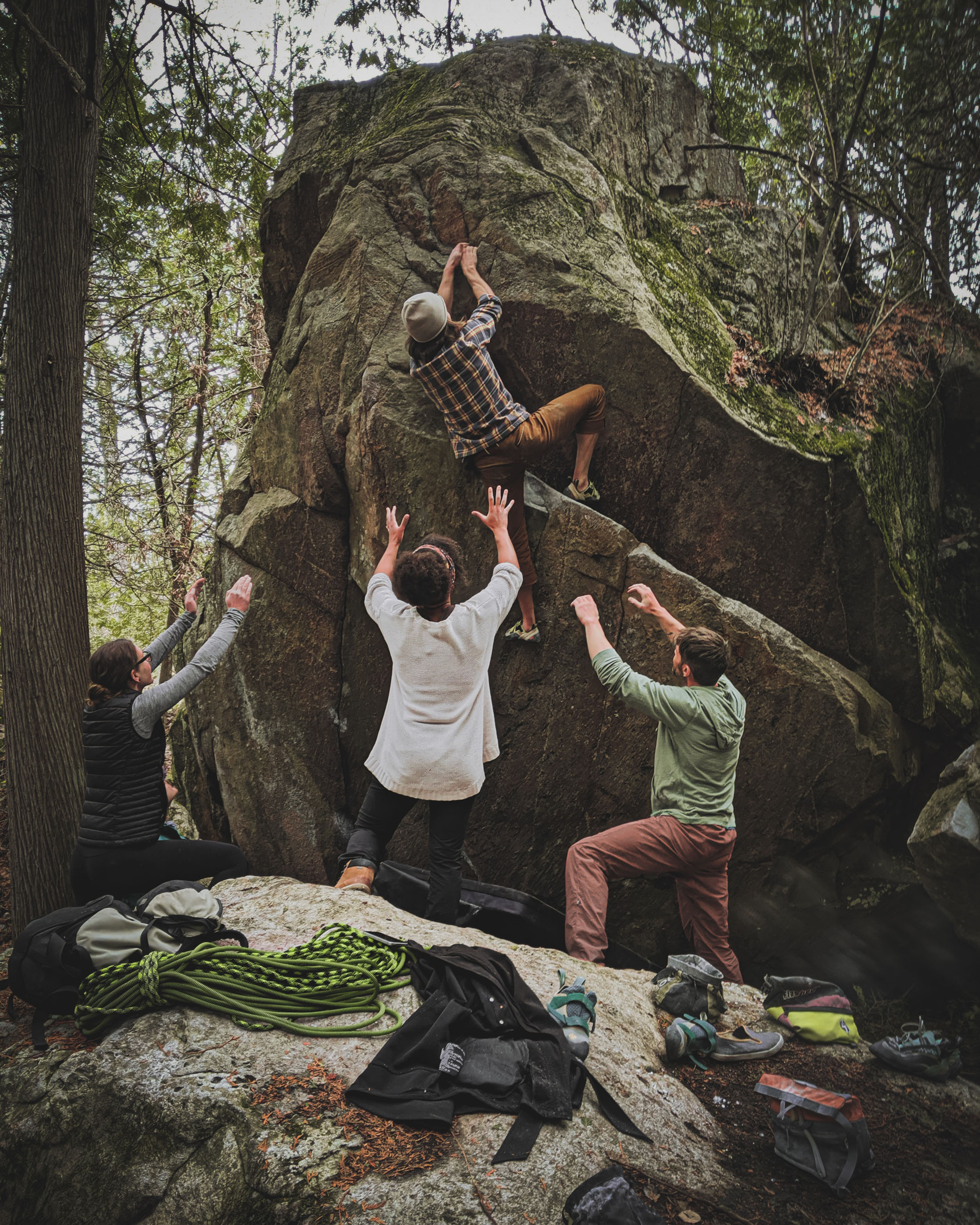 team of rock climbers help eachother succeed climb boulder outdoors pacific northwest