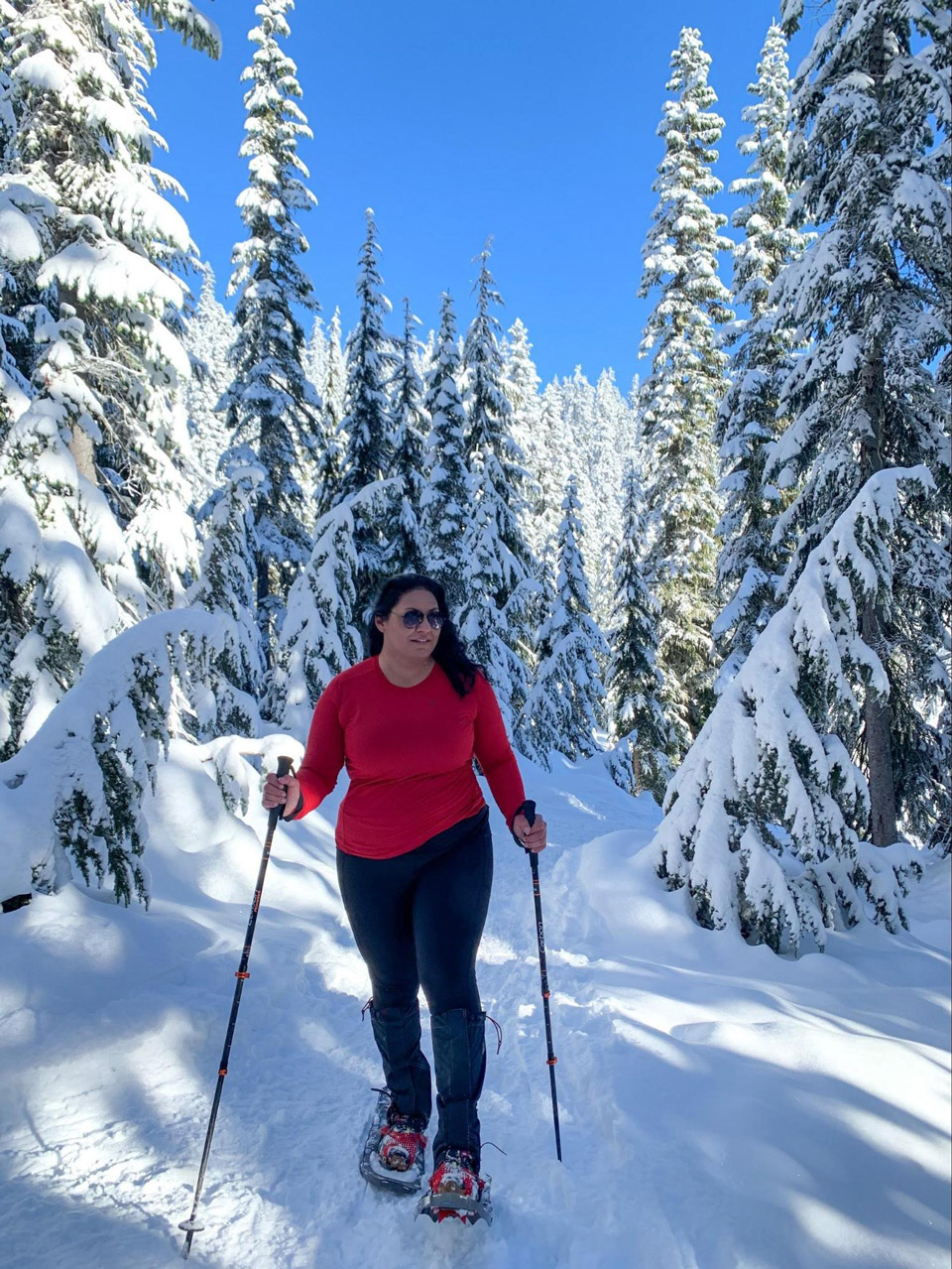Joanna Genovese hiking a snow covered trail with ski poles and snowshoes. In the background is a blue sky and a snow covered forest.