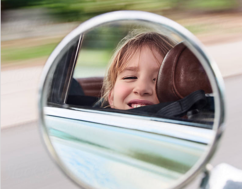 Mirror image of kid looking out car window with blurry background.