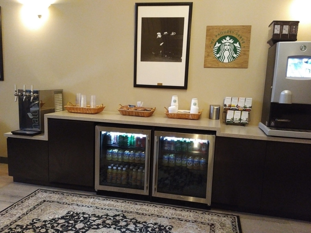 Counter with coffee maker, refrigerators and snacks