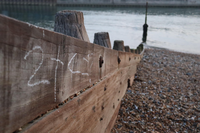 """Wooden groyne that has """"2+4=?"""" written on it in white chalk."""