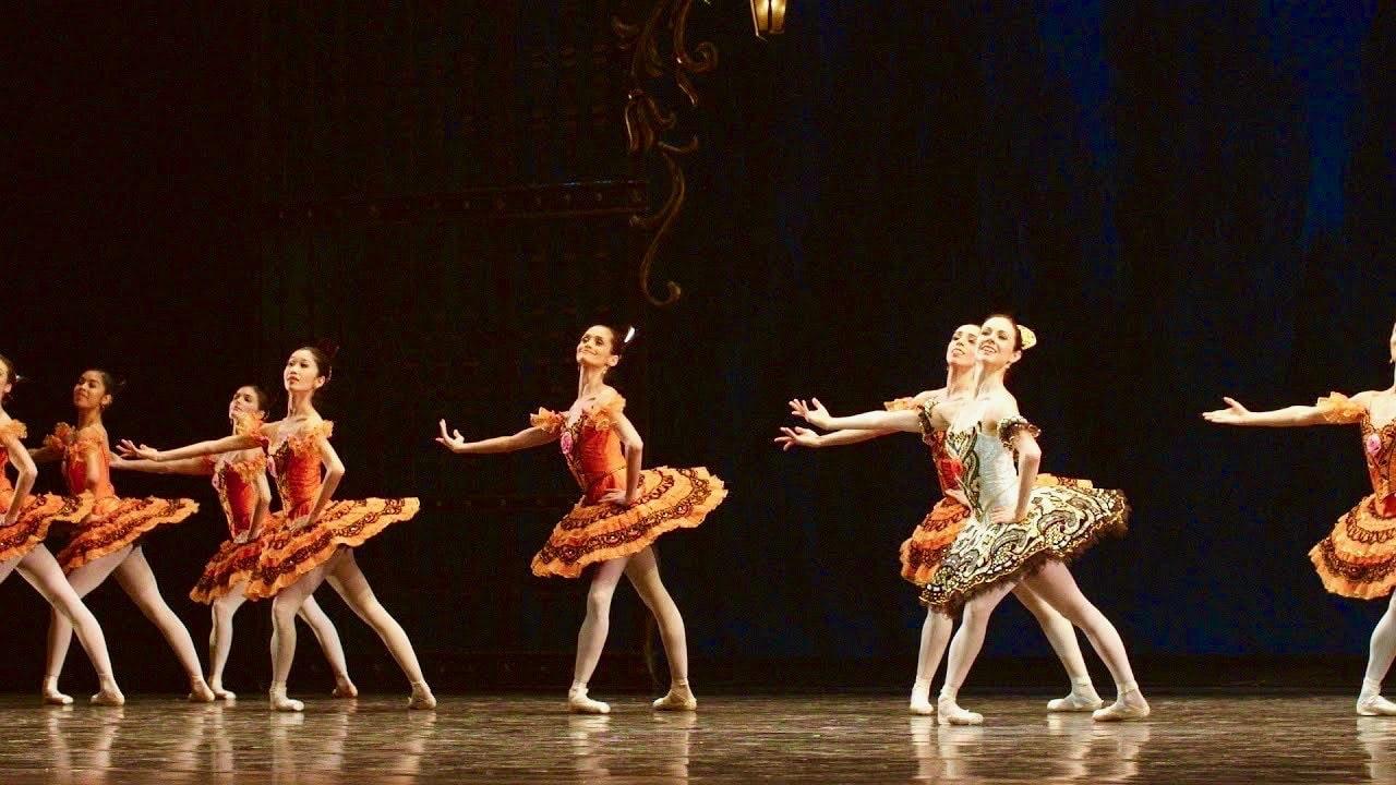 Ballerina in black and white tutu dances with chorus in bright orange tutus.