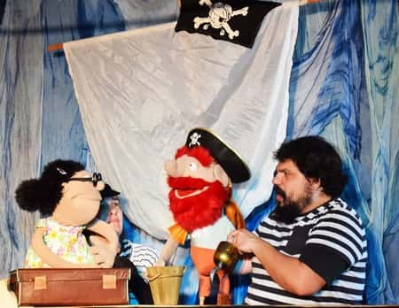 Aleksandros and Aggeliki giving a puppet theater show with a pirate puppet and lady puppet.