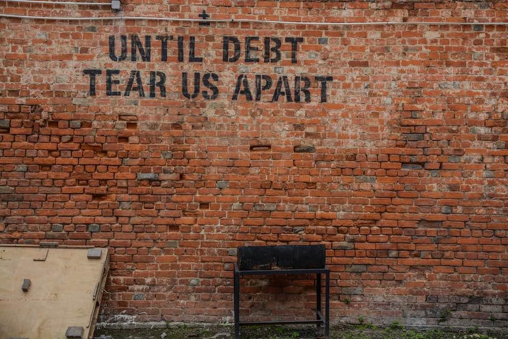 """Until debt tear us apart"" on wall"