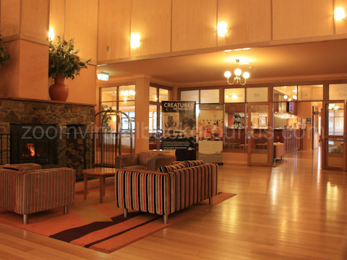 Hotel lobby Virtual Background for Zoom with wooden floor, sofas and soft lighting