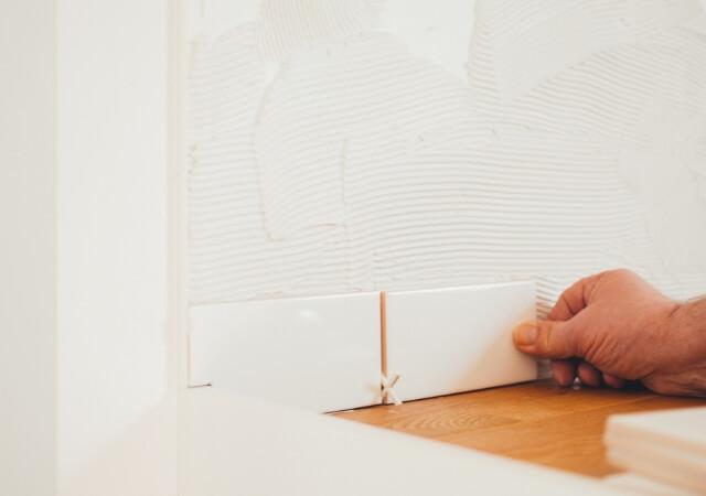 Mão masculina aplicando azulejos na parede.