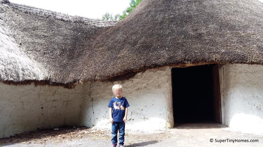A traditional Stone Age house with mudbrick walls and a thatched roof.