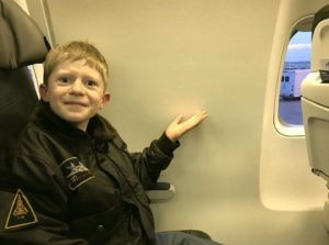 Boy pointing to space without window in a flight