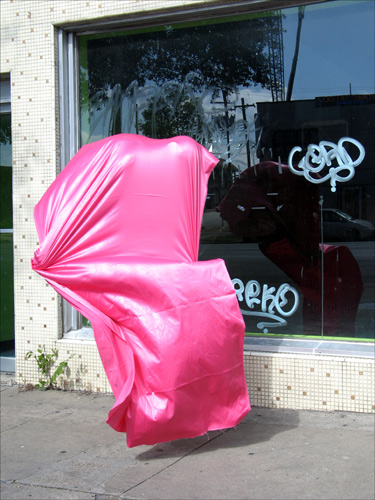 A silk-satin, hot pink mass of fabric seems similarly occupied by a body, but floats in front of a shop window, unmoored.