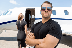A successful man standing in front of a jet