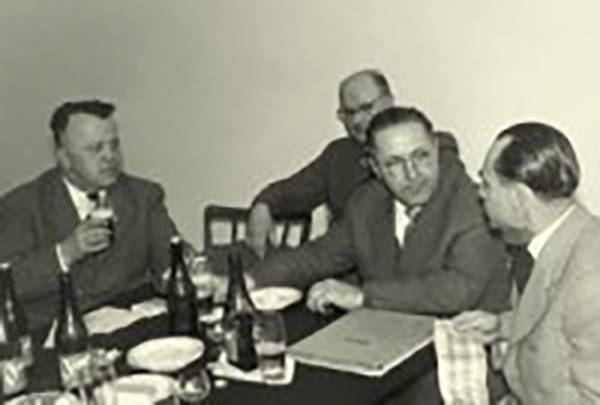 Old photo of a meeting of agricultural machinery dealers at a tavern.