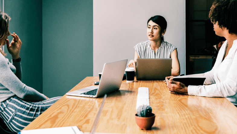 A woman is in a meeting with two men with laptops, pens, files and a plant on a wooden desk in a green room with a whiteboard to discuss picking accounting tools for SMEs as a small business from a Futrli guide #SME