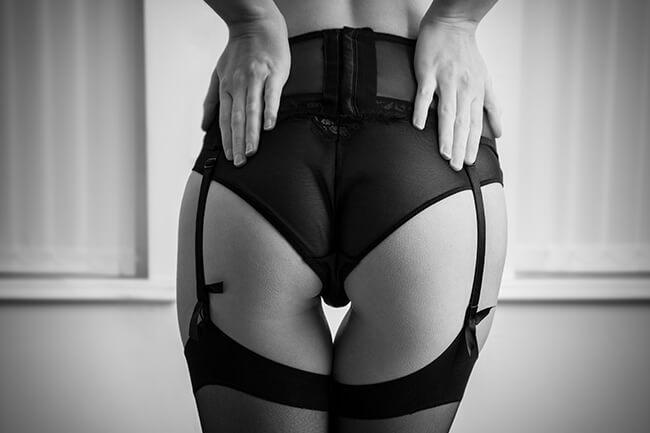 A woman wearing a garter holding her bum.