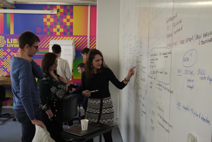 Trois personnes sont debout devant un tableau. L'une d'entre elles, une femme, pointe une phrase sur le tableau pendant que les deux autres regardent, concentrés.