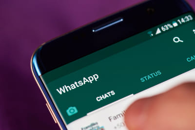 A close-up photo of a phone with Whatsapp open on it.