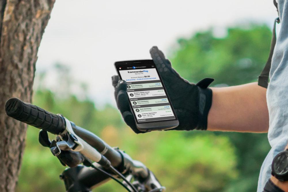 Kommander Pay interface on a bike rider's phone