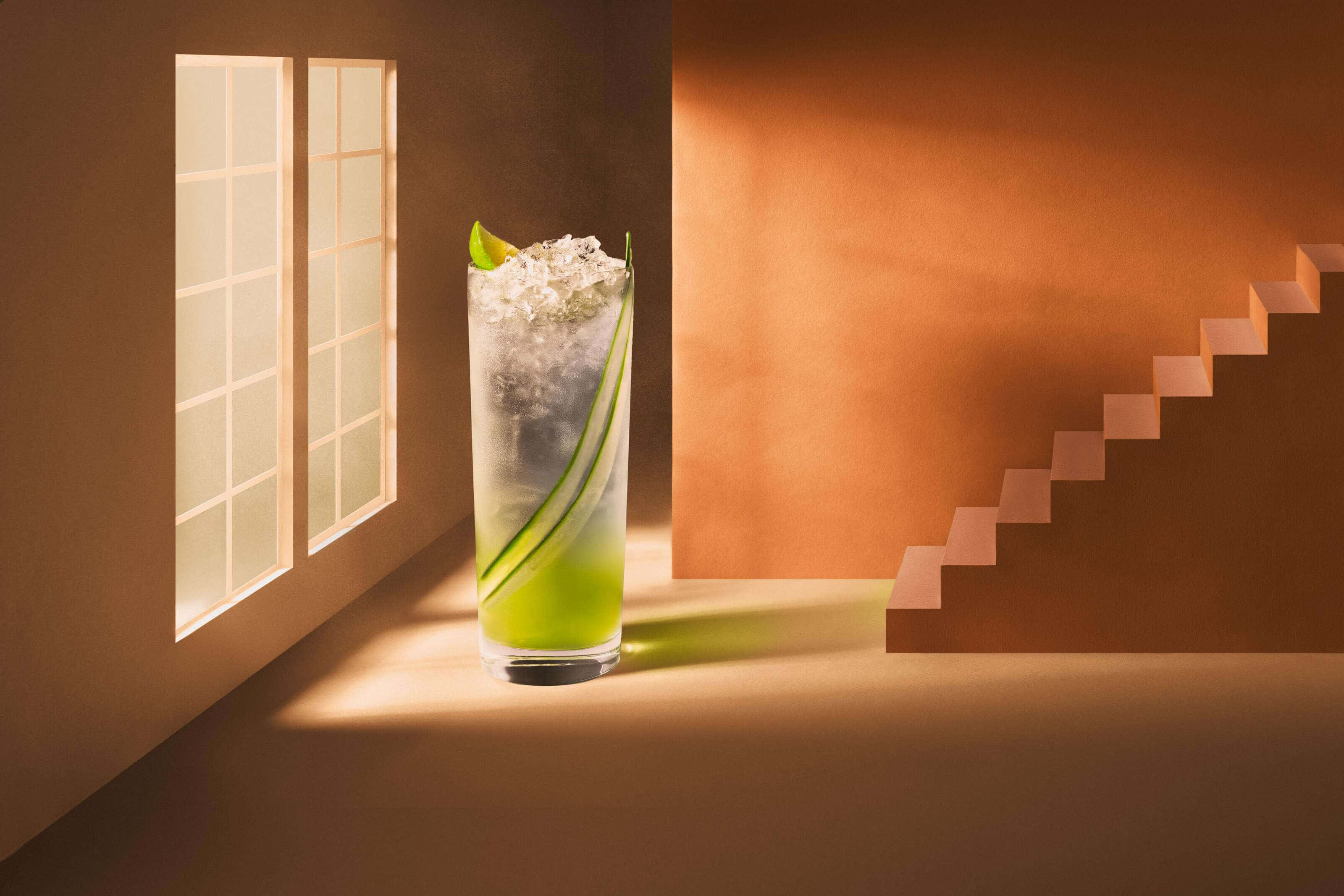 cucumber gin cocktail in set designed to look like a house