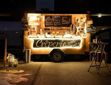 Nachtaufnahme eines schön beleuchteten Creperie Foodtrucks mit gemütlicher Atmosphäre