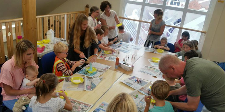 Children and babies making crafts in a library with parents and carers