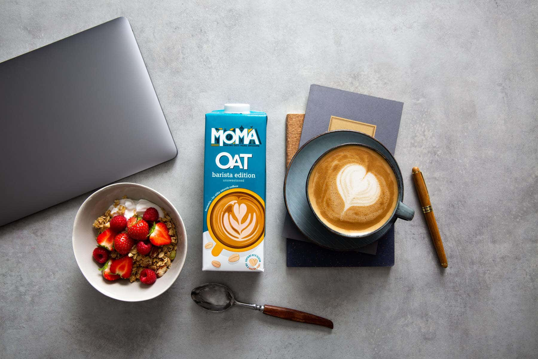 Oat milk carton with a coffee and muesli breakfast on a concrete top