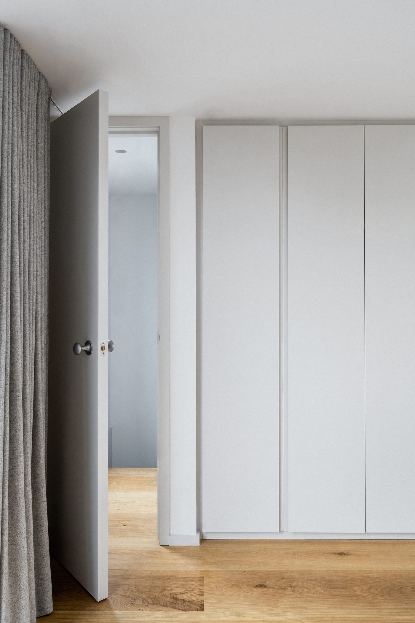 Internal view looking into at the built in wardrobes within the rear dormer extension with light grey joinery and lightweight curtains at Northbrook Road designed by From Works.