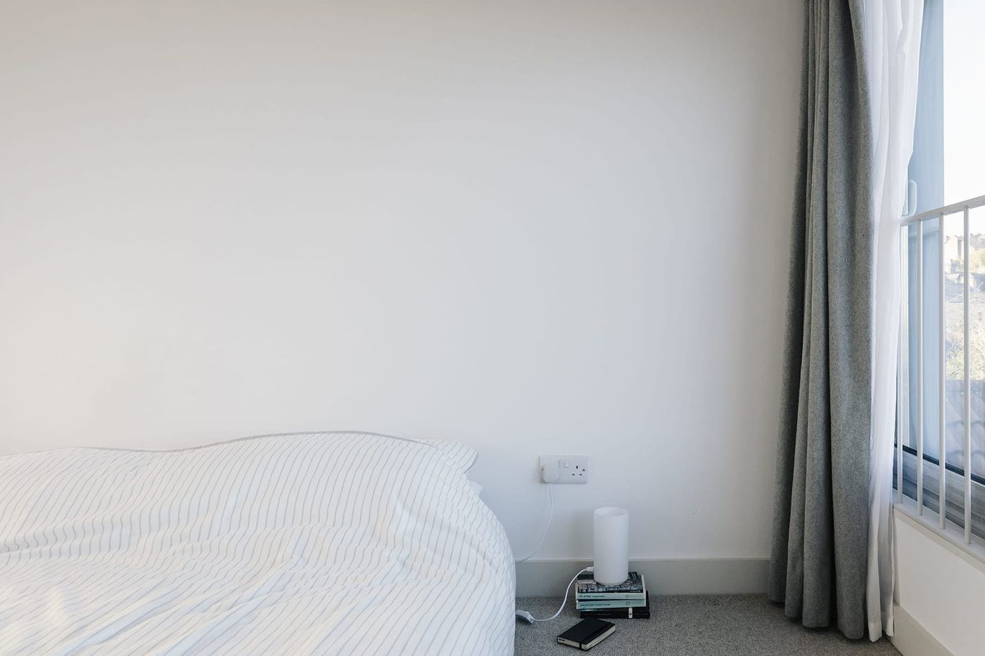 Interior view of white and grey light filled bedroom with juliet balcony and grey felt curtains within From Works loft conversion and rear dormer extension in Walkley, Sheffield.
