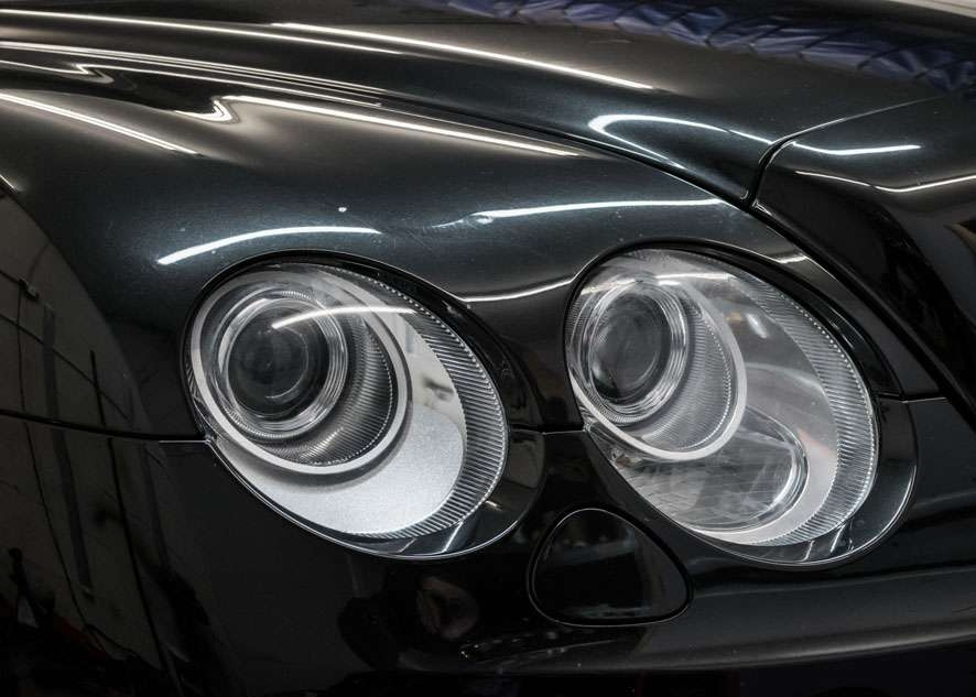 Close up shot of left side Bentley Flying Spur cloudy/foggy headlight before headlight restoration