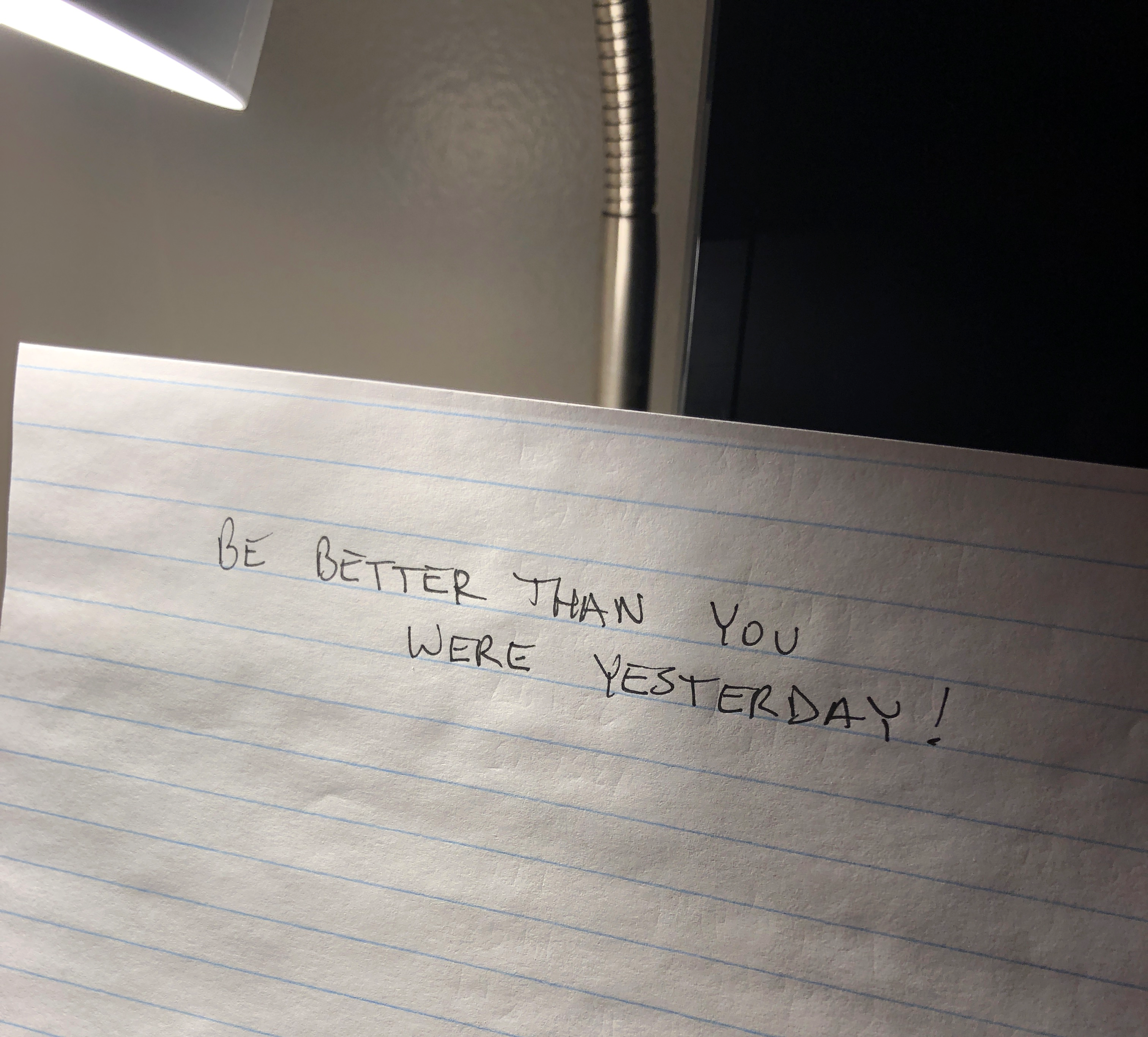 A piece of paper on my side table that reads, 'Be better than you were yesterday'.