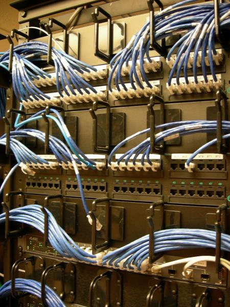 Network switch with lots of wired internet cables going into it, providing internet to lots of devices/areas, from karmarat of FreeImages.