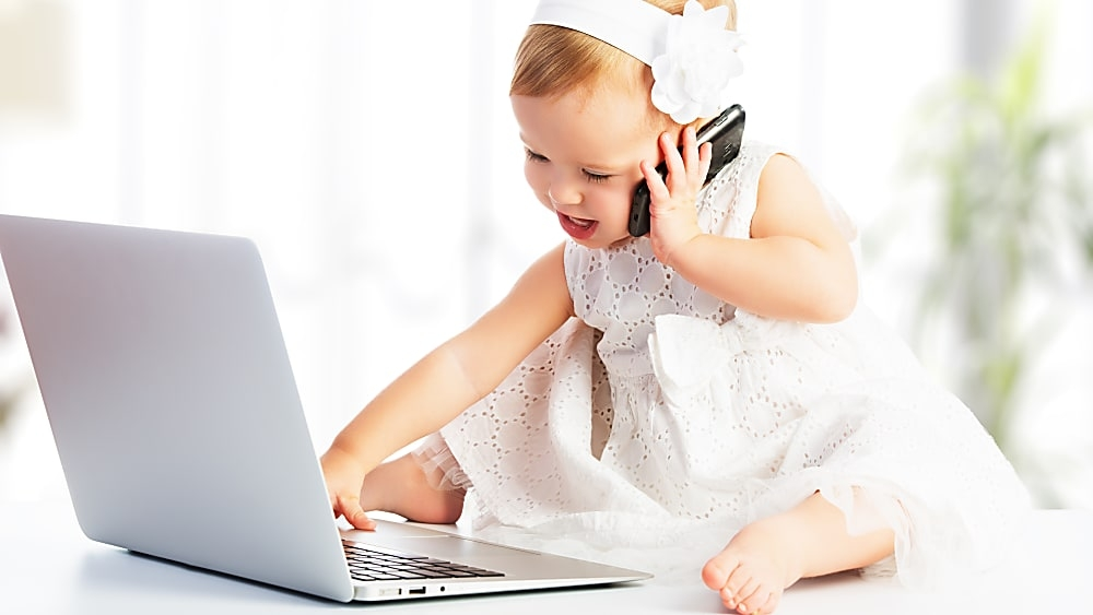 Baby girl talking on a phone in front of a laptop